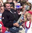 """FILE -- In this file photo taken Oct. 5, 2003, Republican gubernatorial candidate Arnold Schwarzenegger, playfully strums a guitar to the Twisted Sister song, """"We Ain't Going to Take it Anymore,"""" during a campaign rally held at the Capitol in Sacramento, Calif. Schwarzenegger, the former governor, who came to office during California's historic 2003 recall election, will soon be releasing his autobiography, """"Total Recall: My Unbelievably True Life Story.""""(AP Photo/Rich Pedroncelli, file)"""