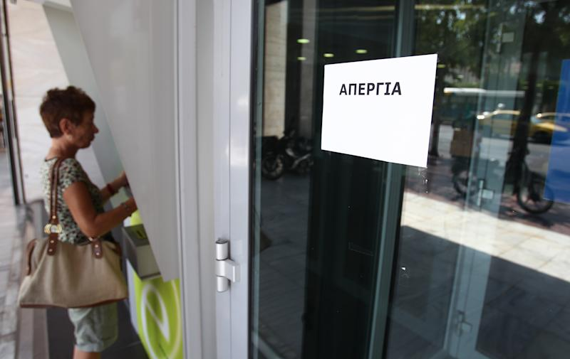 A customer is seen at a bank machine as the paper reads ''Strike'' outside Greece's ATEBank in Athens, Monday, June 30, 2012. The state-run bank was privatized last week, in a no-cash transfer to the private Piraeus Bank. Bank workers on Monday held a 24-hour strike to protest cuts under Greece austerity program. (AP Photo/Thanassis Stavrakis)