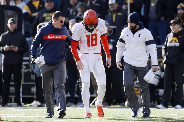 Illinois quarterback Brandon Peters (18) is helped off the field after getting injured during the second half of an NCAA college football game against Iowa, Saturday, Nov. 23, 2019, in Iowa City, Iowa. Iowa won 19-10. (AP Photo/Charlie Neibergall)