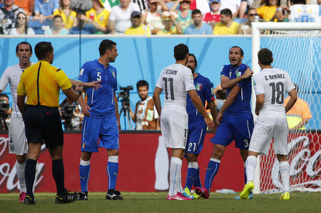 Italy's Giorgio Chiellini (2nd R) complains to referee Marco Rodriguez of Mexico (2nd L) during their 2014 World Cup Group D soccer match against Uruguay at the Dunas arena in Natal June 24, 2014. Chiellini claimed that Uruguay's Luis Suarez bit him on his shoulder during a challenge. REUTERS/Yves Herman