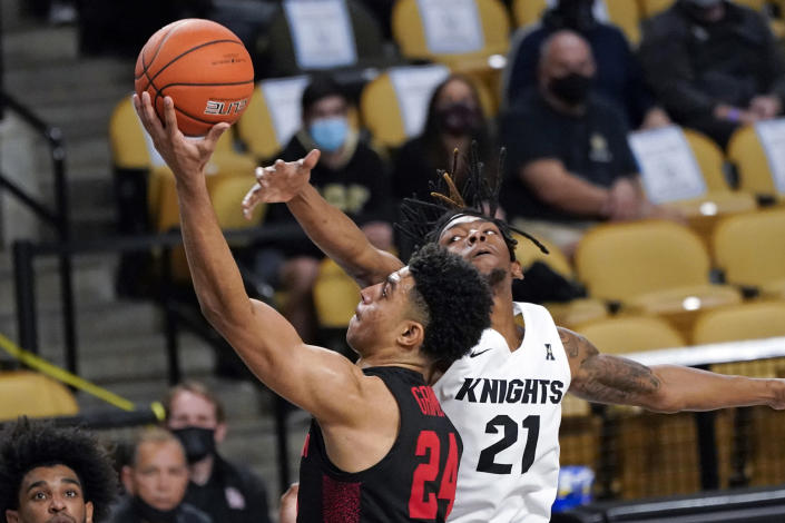 Houston guard Quentin Grimes (24) gets past Central Florida forward C.J. Walker (21) for a shot during the second half of an NCAA college basketball game, Saturday, Dec. 26, 2020, in Orlando, Fla. (AP Photo/John Raoux)