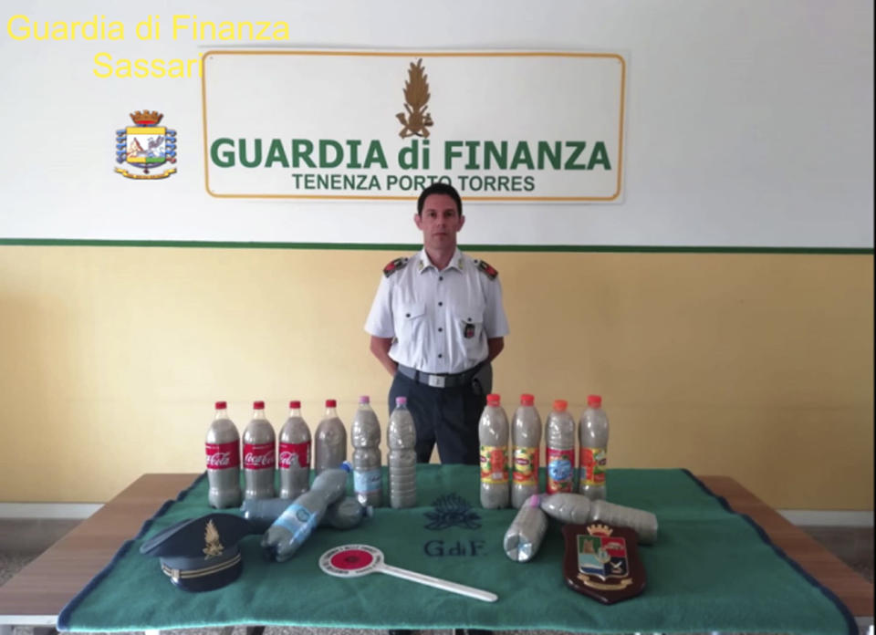 This picture taken on Aug. 16, 2019 and made available Tuesday, Aug. 20, 2019 by the Finance Police of the Sardinian port of Porto Torres, Italy, shows 14 plastic bottles of sand seized from a French couple in the trunk of the couple's car. The French couple could face up to six years in jail for taking around 40 kg (88.1lbs) of the island's famed white sand from Chia beach, which is protected as a public good. (Italian Finance Police via AP)