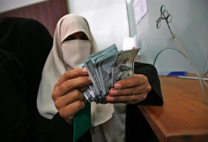 A Palestinian woman counts her money after receiving her salary in Rafah in the southern Gaza Strip on November 9, 2018 (AFP Photo/SAID KHATIB)