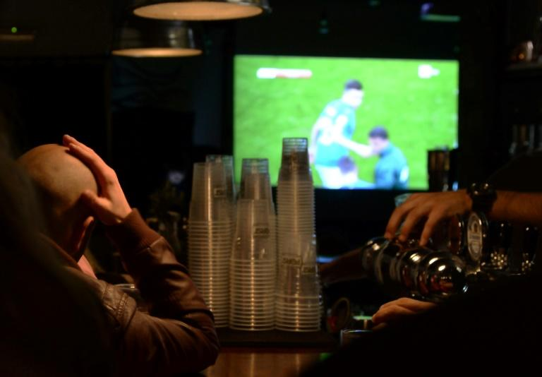 Italian supporters watch the FIFA World Cup 2018 qualification football match Italy vs Sweden TV broadcast at a pub in Rome, on November 13, 2017