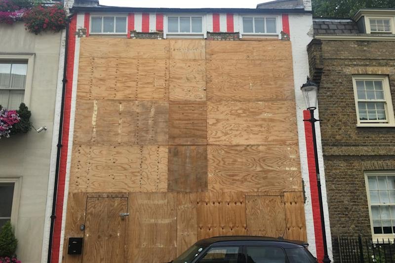 The striped house was boarded up and ready for demolition in July last year. (Barney Davis)