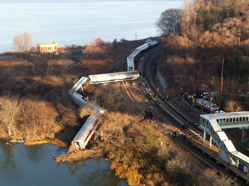 FILE- In this Dec. 1, 2013 file photo, cars from a Metro-North passenger train are scattered after the train derailed in the Bronx neighborhood of New York. Although the train had an automatic breaking system that might have prevented the crash, but at the time it wasn't set up to enforce speed limits on the curve where the wreck happened. The accident killed four people and injured over 60. (AP Photo/Edwin Valero, File)