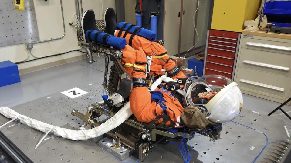 A dummy in an orange space suit sits upside down in a chair