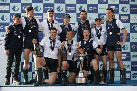 The Oxford crew celebrate with the trophy after winning the men's Boat Race