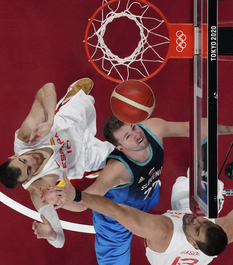 Slovenia's Luka Doncic, center, goes to the basket between Spain's Victor Claver, left, and Marc Gasol, right, during a men's basketball game at the 2020 Summer Olympics, Wednesday, July 28, 2021, in Saitama, Japan. (Brian Snyder/Pool Photo via AP)
