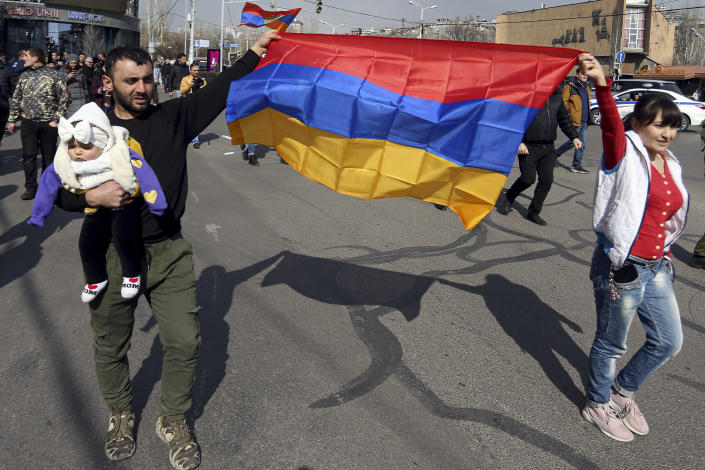 Supporters of Armenian Prime Minister Nikol Pashinyan march with Armenian national flags toward the main square in Yerevan, Armenia, Thursday, Feb. 25, 2021. Armenia's prime minister has spoken of an attempted military coup after facing the military's General Staff demand to step down. The developments come after months of protests sparked by the nation's defeat in the Nagorno-Karabakh conflict with Azerbaijan. (Stepan Poghosyan/PHOTOLURE via AP)
