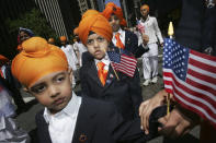 FILE - In this Saturday, April 29, 2006 photo, children holding U.S. flags march down Broadway during the 19th Annual Sikh Day Parade in New York. Since Sept. 11, 2001, many Sikhs have been mistaken for Muslims and have become targets. As a result, they have been at the forefront of civil rights advocacy against religious and racial profiling. (AP Photo/Hiroko Masuike, File)