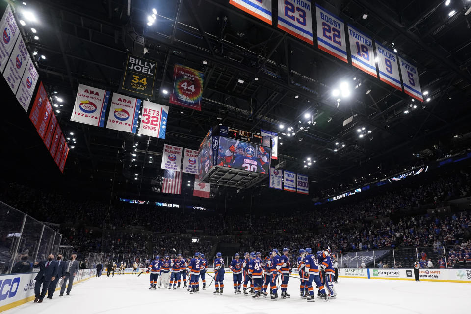 The New York Islanders head coach Barry Trotz, left, leaves the ice as his team celebrates after Game 4 of an NHL hockey Stanley Cup first-round playoff series against the Pittsburgh Penguins, Saturday, May 22, 2021, in Uniondale, N.Y. The Islanders won 4-1. (AP Photo/Frank Franklin II)