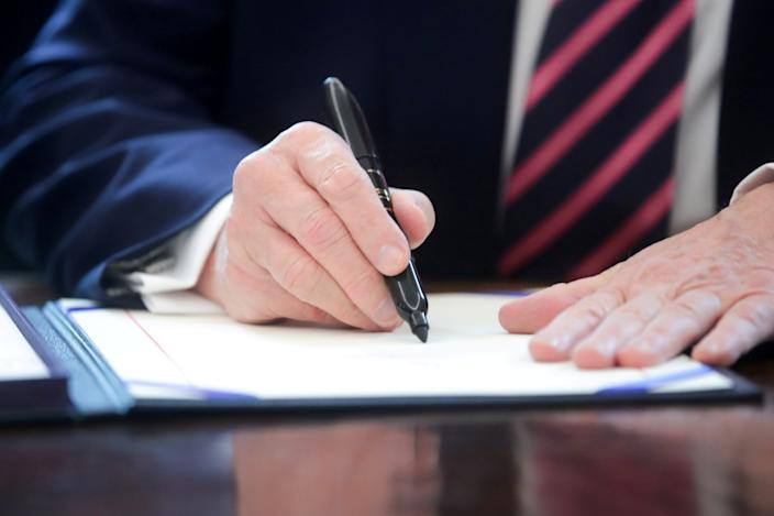 FILE PHOTO: U.S. President Donald Trump signs the Paycheck Protection Program and Health Care Enhancement Act financial response to the coronavirus disease (COVID-19) outbreak, in the Oval Office at the White House in Washington, U.S. April 24, 2020.  REUTERS/Jonathan Ernst/File Photo