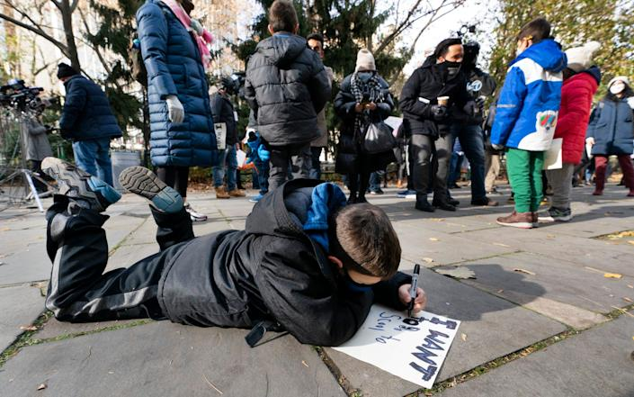 """Benjamin Saling, a first grader from Queens, makes a sign that says """"I want to be in scool"""" before joining a protest against closures in front of New York's City Hall - AP"""