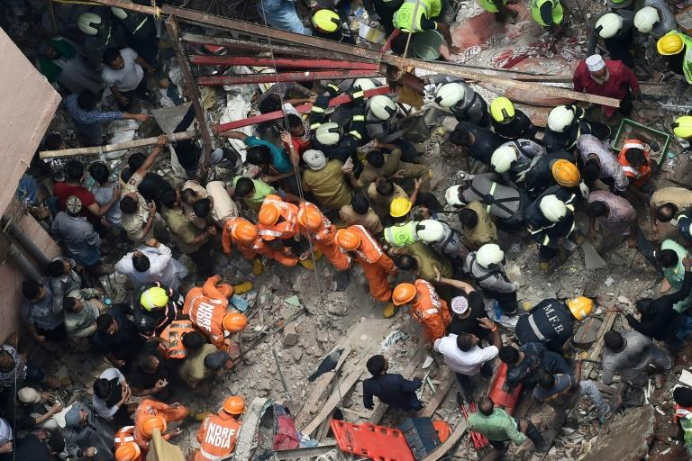 Indian National Disaster Response Force and Indian fire brigade personnel search for survivors among the debris from a building collapse that killed 10 people in Mumbai during heavy monsoon rains (AFP Photo/Punit PARANJPE)
