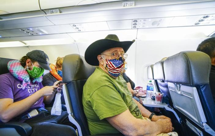 """<span class=""""caption"""">Passengers onboard an American Airlines flight to Charlotte, North Carolina, from San Diego, California. </span> <span class=""""attribution""""><a class=""""link rapid-noclick-resp"""" href=""""https://www.gettyimages.com/detail/news-photo/passengers-onboard-an-american-airlines-flight-to-charlotte-news-photo/1214261343?adppopup=true"""" rel=""""nofollow noopener"""" target=""""_blank"""" data-ylk=""""slk:Sandy Huffaker/Getty Images"""">Sandy Huffaker/Getty Images</a></span>"""