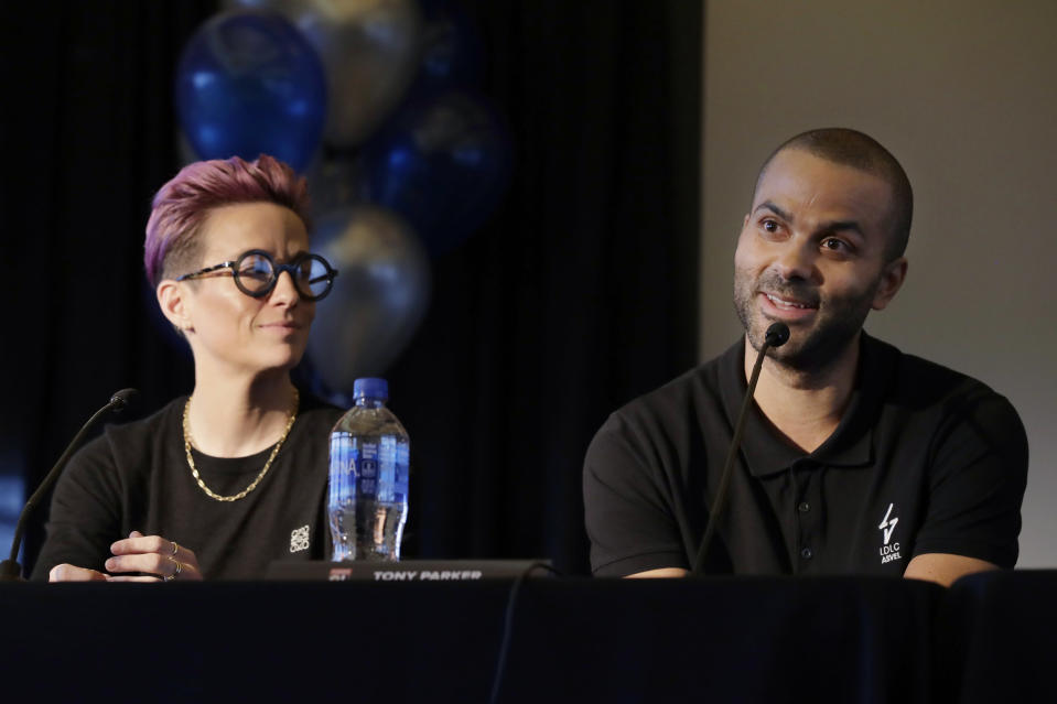 Megan Rapinoe, left, a forward with the National Women's Soccer League's Reign FC and the U.S. Women's National Team, listens as former NBA basketball star Tony Parker, right, speaks, Thursday, Dec. 19, 2019, during a news conference to announce that OL Groupe, the parent company of Olympique Lyonnais, is buying Reign FC in a transaction expected to close in January 2020. Parker will be a minority owner of the team and Reign FC will continue to play its home games at Cheney Stadium, the venue it shares with the Triple-A minor league baseball team the Tacoma Rainiers. (AP Photo/Ted S. Warren)