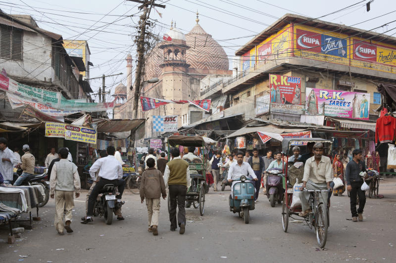 Agra, Uttar Pradesh, India, South Asia. Shoppers and stalls at Kinari bazaar. The Jama Masjid mosque in the background dates from 1648