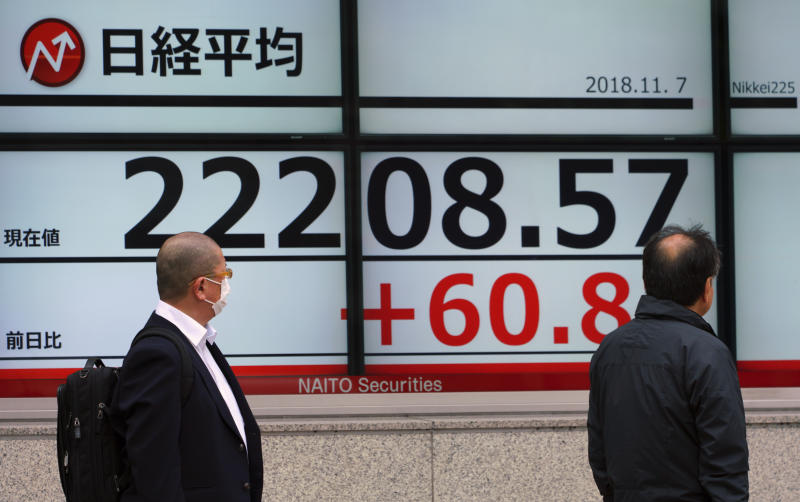 Men look at an electronic stock board showing Japan's Nikkei 225 index at a securities firm in Tokyo Wednesday, Nov. 7, 2018. Asian shares were mostly higher Wednesday as investors awaited results from the U.S. midterm elections, which could have an impact on the global economy and trade. (AP Photo/Eugene Hoshiko)