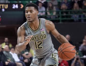 FILE - In this March 2, 2020, file photo, Baylor's Jared Butler (12) drives against Texas Tech during the first half of an NCAA college basketball game in Waco, Texas. Seniors Luke Garza of Iowa and Baylor's Jared Butler headline The Associated Press 2020-21 preseason All-America team, announced Wednesday, Nov. 11. (AP Photo/Chuck Burton, File)