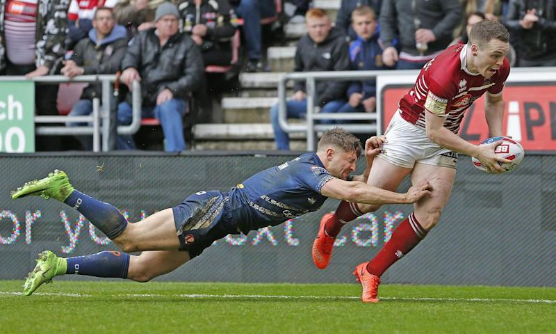 Wigan's Joe Burgess scores the fourth try against St Helens, despite a valiant effort by Tommy Makinson