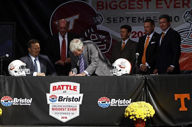 """Virginia Tech head football coach Frank Beamer signs the contract as Marcus Smith, president of Speedway Motorsports, seated, Virginia Tech athletic director Jim Weaver, standing at left, Tennessee athletic director Dave Hart, third from right, Tennessee head football coach Butch Jones, second from right, and Jerry Caldwell, general manager of Bristol Motor Speedway, right, watch during a press conference at Bristol Motor Speedway Monday, Oct. 14, 2013, in Bristol, Tenn. Tennessee and Virginia Tech will finally play a football game at Bristol Motor Speedway in what is being billed as the """"Battle of Bristol."""" (AP Photo/Wade Payne)"""