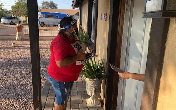 """A well-built Latino woman with tattooed arms, wearing a red T-shirt that says """"ONE JOB IS ENOUGH"""" and protective face masks, stands on a doorstep, leaning slightly forward as she speaks to an unseen voter. All that can be seen other person is a hand reaching out of the door, holding a pamphlet they have just been given. In the background is a gravel yard, and beyond that low tan-coloured houses, with an old silver and blue caravan parked in front of one of them - Laurence Dodds/Telegraph"""