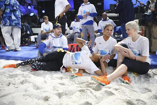 Alicia Quarles, television personality for E! News, lays out on the sideline alongside Chrissy Teigen, Sports Illustrated swimsuit model, second from right, and Gillian Jacobs, actress, right, in between players during the Direct TV Beach Bowl at Pier 40, Saturday, Feb. 1, 2014, in New York. (John Minchillo/AP Images for Direct TV)
