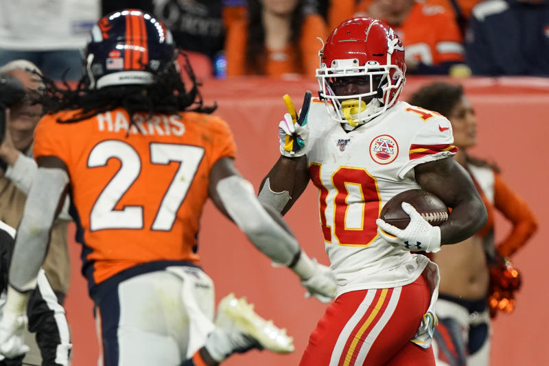 Kansas City Chiefs wide receiver Tyreek Hill (10) signals to Denver Broncos cornerback Davontae Harris (27) as he scores a touchdown during the second half of an NFL football game, Thursday, Oct. 17, 2019, in Denver. (AP Photo/Jack Dempsey)