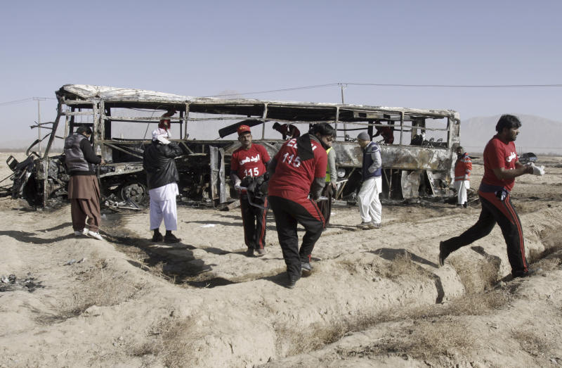 Pakistani volunteers carry a lifeless body out of a bus targeted in a suicide bombing in Quetta, Pakistan, Sunday, Dec. 30, 2012. A suicide bomber driving a vehicle packed with explosives rammed into a bus carrying Shiite Muslim pilgrims in southwest Pakistan on Sunday, killing several people, a government official and eyewitnesses said. (AP Photo/Arshad Butt)