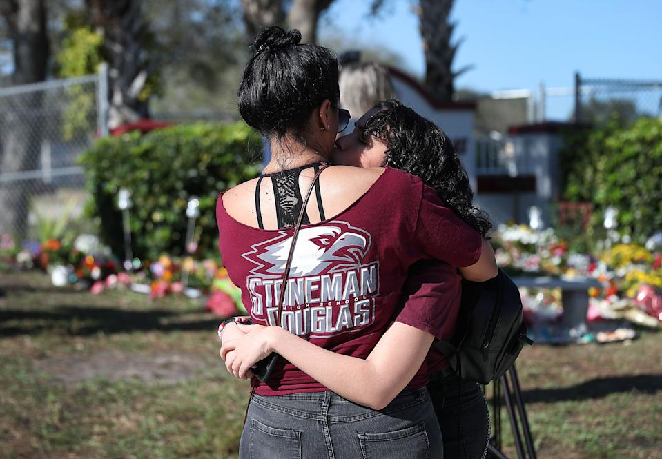 People hug as they visit a memorial set up near the Marjory Stoneman Douglas High School in honor of those killed. (Photo by Joe Raedle/Getty Images)