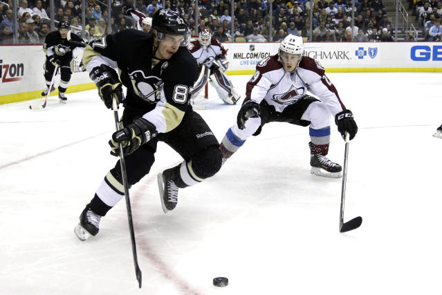 Pittsburgh Penguins' Sidney Crosby (87) works the puck in the corner against Colorado Avalanche's Nathan MacKinnon (29) in the second period of an NHL hockey game in Pittsburgh Monday, Oct. 21, 2013. (AP Photo/Gene J. Puskar)