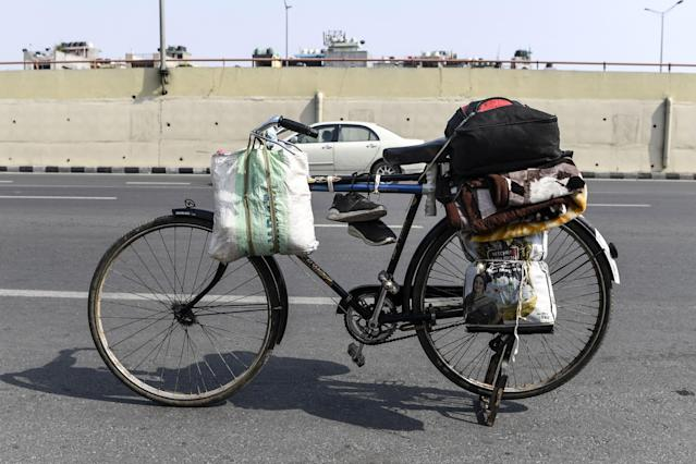 A bicycle of a migrant worker is loaded with belongings at a roadside. (Photo by SAJJAD HUSSAIN/AFP via Getty Images)