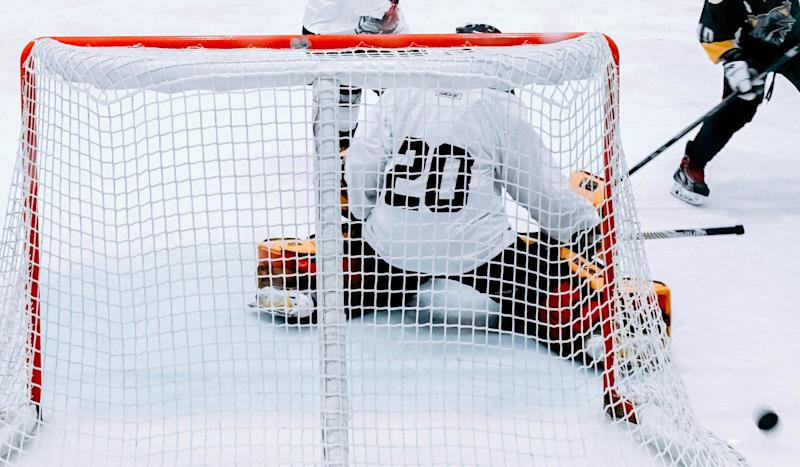 A hockey player shoots and misses as a goalie makes a save.
