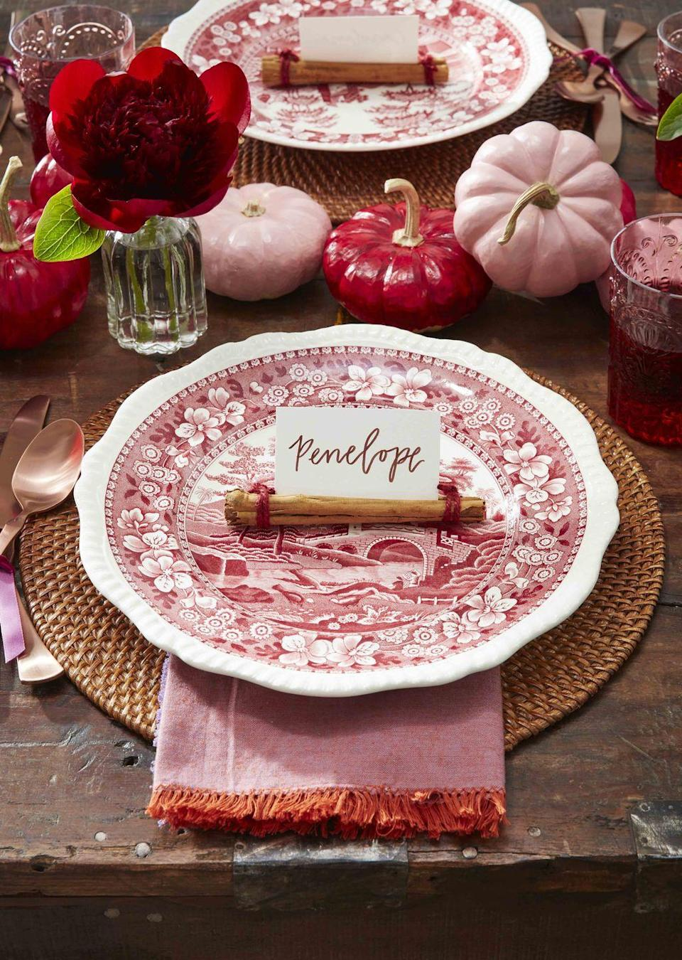 <p>Welcome guests with a the scent of warm spices. <strong><br></strong></p><p><strong>Make the holder</strong>: Wrap the ends of cinnamon sticks in red twine and slip place cards in the stick's natural crevice to create placecards.</p>