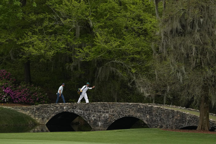 Justin Rose, of England, crosses the Hogan Bridget with his caddie David Clark during the first round of the Masters golf tournament on Thursday, April 8, 2021, in Augusta, Ga. (AP Photo/Charlie Riedel)