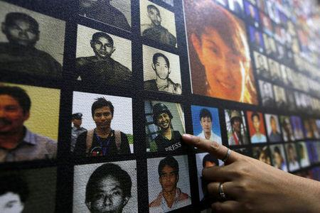 A staff member points at the wall of political prisoners at the Assistance Association for Political Prisoners (Burma) museum in Yangon, Myanmar May 17, 2018. REUTERS/Ann Wang/Files