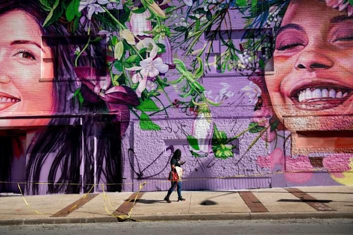 A woman walks past a mural in Baltimore's Charles Village neighborhood