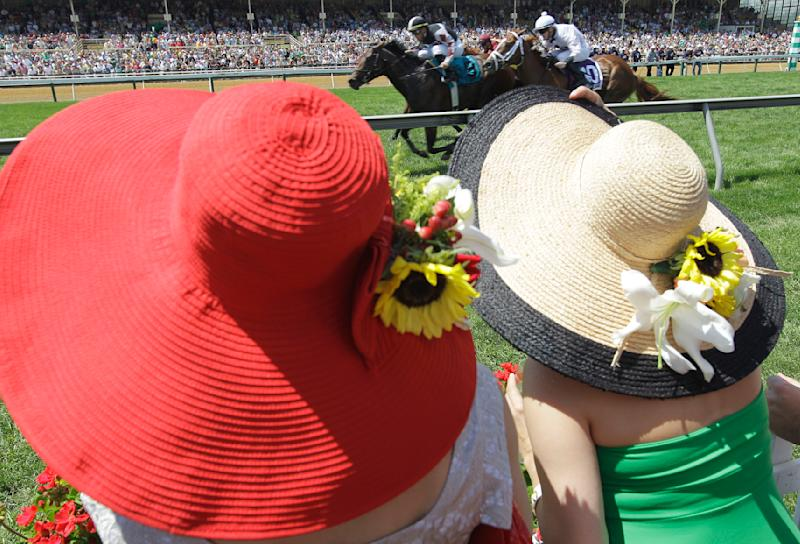 Spectators with wide-brimmed watch the James W. Murphy Stakes from Turfside Terrace at Pimlico Race Course, Saturday, May 21, 2011, in Baltimore. The Murphy Stakes race is an undercard to the Preakness Stakes. (AP Photo/Steve Helber)