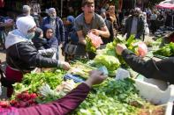 People shop for vegetables at a souk in Beirut