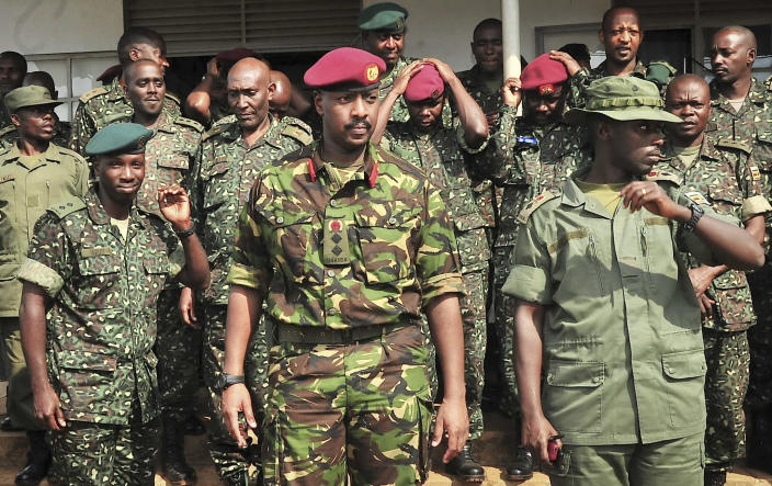 In this photo taken Thursday, Aug. 16, 2012 and made available Thursday may 9, 2013 by Uganda's Presidency, Ugandan Special Forces Group (SFG) Brigadier Muhoozi Kainerugaba, center, who is the son of President Yoweri Museveni, poses for a photograph with other officers at the Kasenyi SFG camp, east of Kampala in Uganda. A Ugandan military general in a letter dated Monday, April 29, 2013 has accused the country's president of trying to ensure his son replaces him as the country's leader, the first top military official to raise concerns about President Yoweri Museveni's succession after nearly three decades in power. (AP Photo/Uganda Presidency)