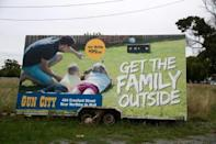 Anger has focussed on Gun City's billboard on a busy highway showing a man teaching two children how to shoot