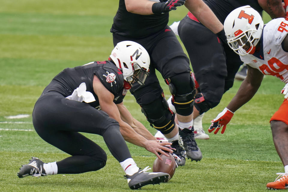 Nebraska quarterback Luke McCaffrey, left, and Illinois defensive lineman Owen Carney Jr. (99) go after the ball following a bad snap in the first half of an NCAA college football game in Lincoln, Neb., Saturday, Nov. 21, 2020. Nebraska recovered the ball. (AP Photo/Nati Harnik)