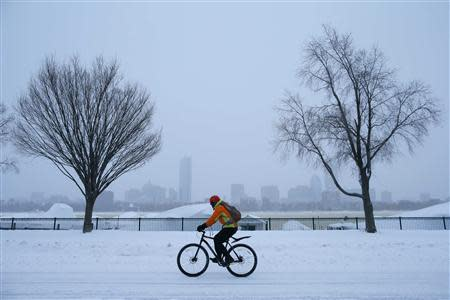 A cyclist rides along snow covered Memorial Drive during a winter nor'easter snow storm in Cambridge, Massachusetts January 3, 2014. REUTERS/Brian Snyder