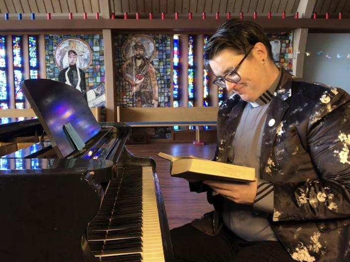 Rev. Megan Rohrer sits at the piano in a church and looks down at an open book.