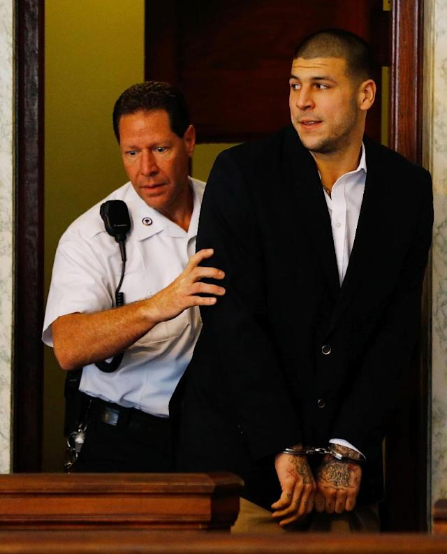 This photo taken on August 21, 2013 shows Aaron Hernandez as he is escorted into the courtroom of the Attleboro District Court during his hearing in North Attleboro, Massachusetts (AFP Photo/Jared Wickerham)