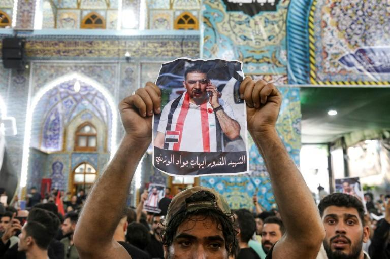 A mourner brandished a picture of murdered Iraqi anti-government activist Ihab al-Wazni during his funeral at the Imam Hussein Shrine in the central Shiite shrine city of Karbala in early May