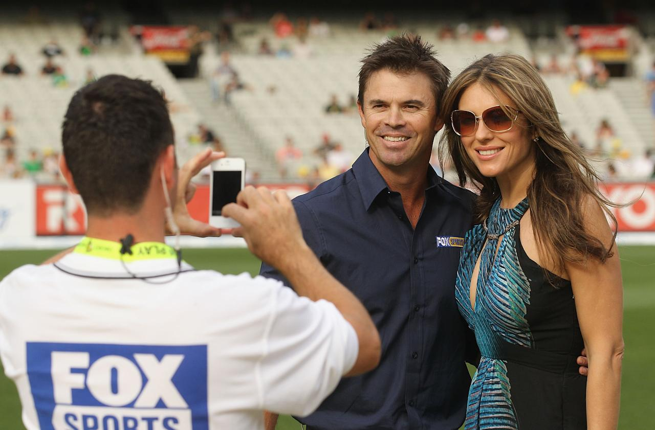 MELBOURNE, AUSTRALIA - DECEMBER 17:  Liz Hurley poses with former cricketer and Fox Sports presenter Greg Blewett during the T20 Big Bash League match between the Melbourne Stars and the Sydney Thunder at Melbourne Cricket Ground on December 17, 2011 in Melbourne, Australia.  (Photo by Hamish Blair/Getty Images)