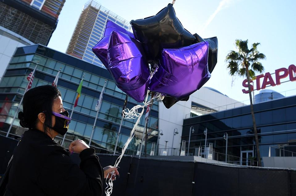 Josie Alavarez does the sign of the cross before releasing balloons on the one-year anniversary of Kobe Bryant's death.