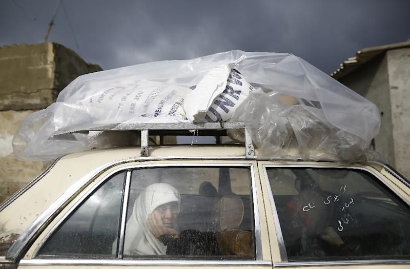 A Gazan woman picks up a food parcel from the UN agency for Palestinian refugees which says it faces its worst funding crisis ever after the White House froze tens of millions of dollars in contributions (AFP Photo/MOHAMMED ABED)